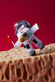 Spaceman explores Mars. Light bulb toy dressed in spacesuit and