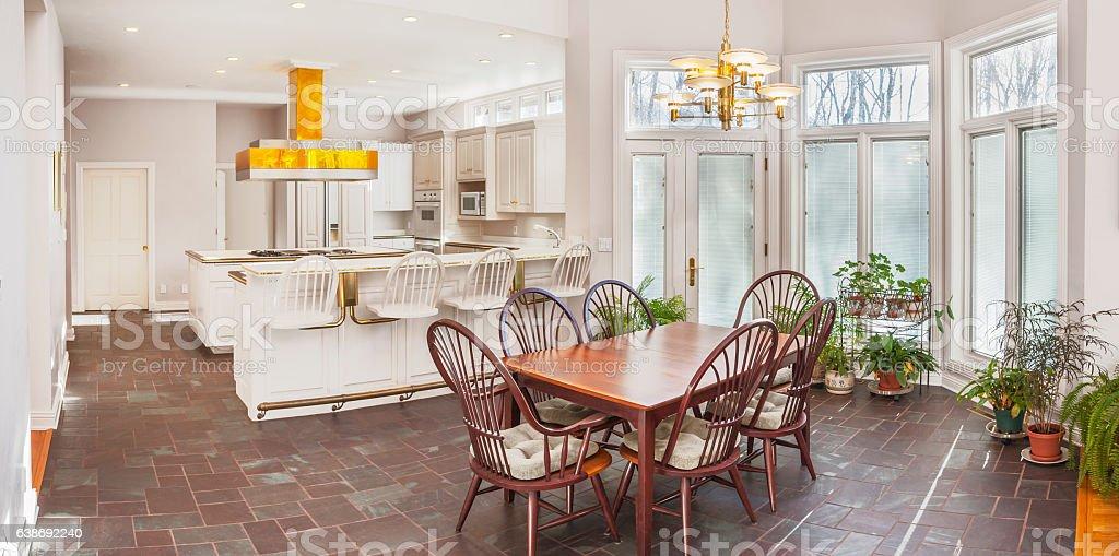 Spacious casual breakfast nook adjoining modern white kitchen stock photo