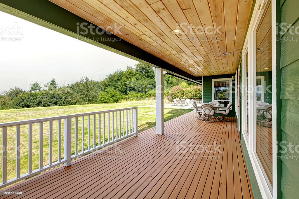Spacious wooden deck with patio table set. Backyard view stock photo