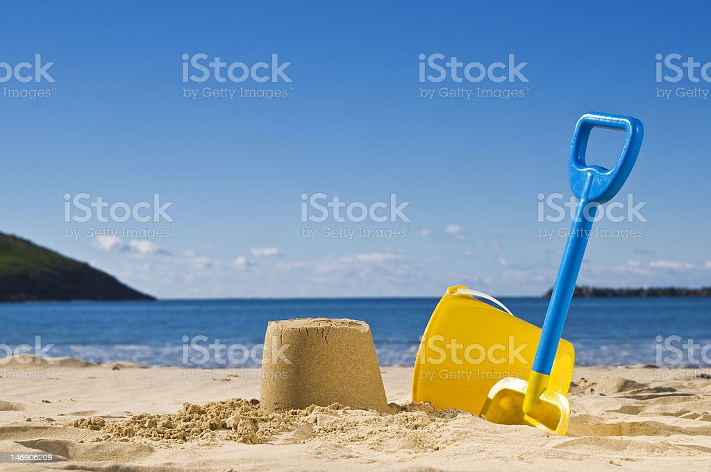 Spade and bucket at the beach stock photo