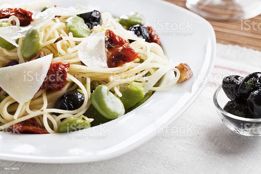 spagetthi with fava beans, olives and dried tomatoe stock photo
