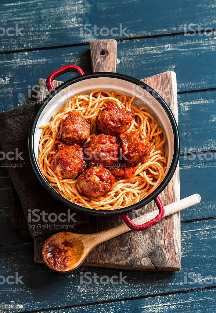 Spaghetti and meatballs in tomato sauce on wooden rustic board. stock photo