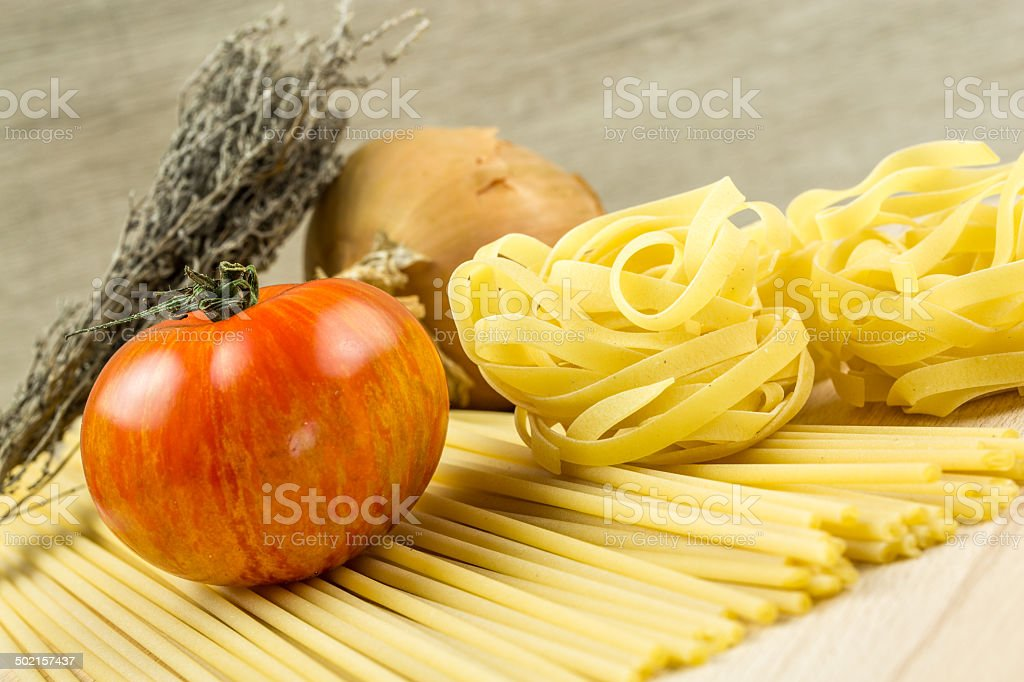 Spaghetti and Tagliatelle pasta and tomatoes with herbs royalty-free stock photo