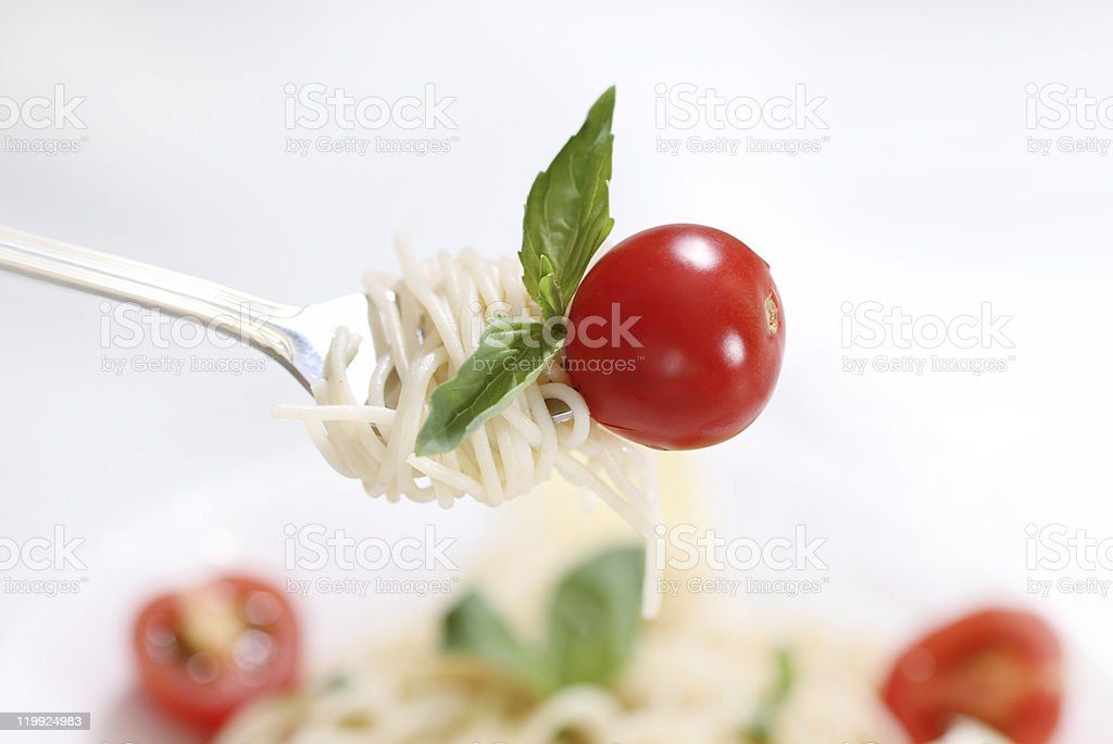 Spaghetti, basil and tomato on fork royalty-free stock photo