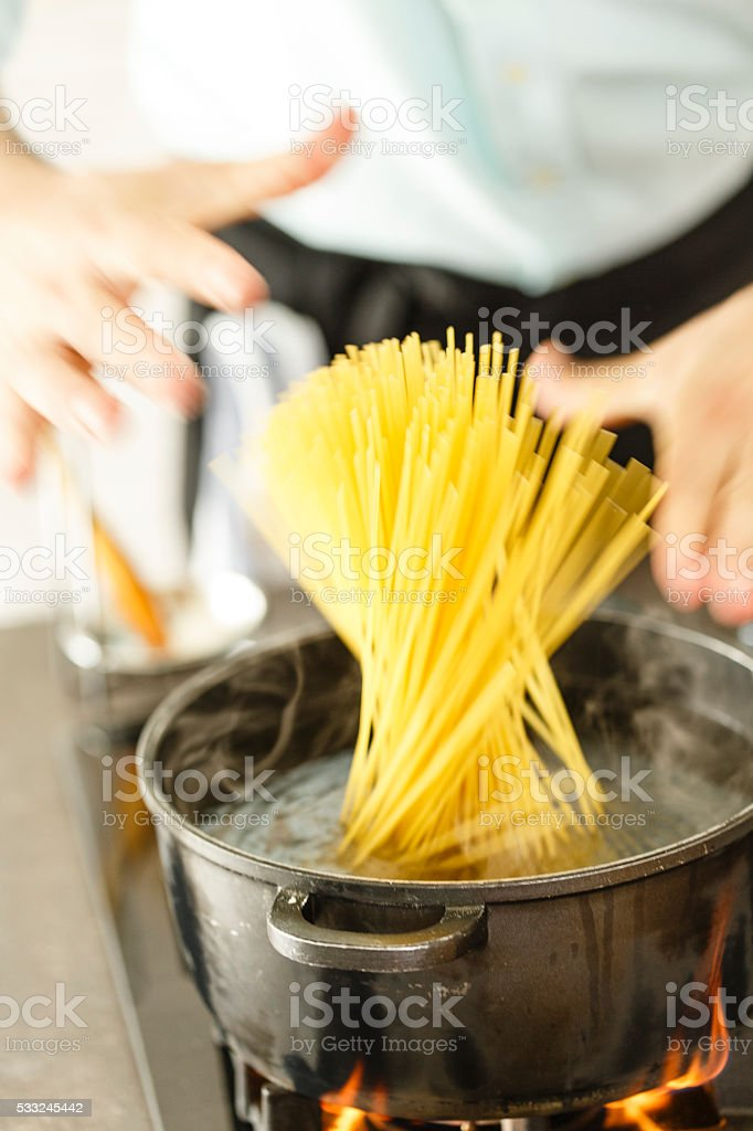 Spaghetti being put into a pan of boiling water stock photo