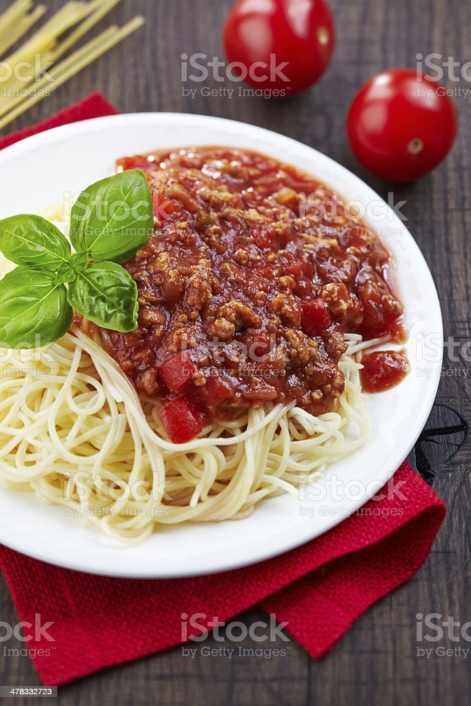Spaghetti bolognese and green basil leaf on white plate royalty-free stock photo