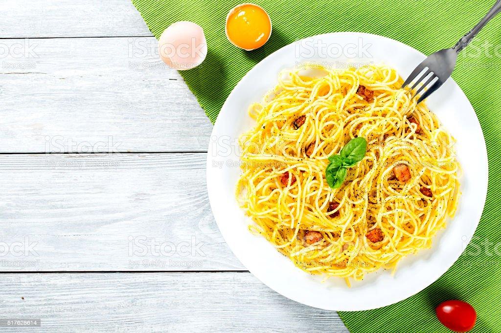 Spaghetti carbonara, basil, eggs yolk, grated parmesan cheese stock photo
