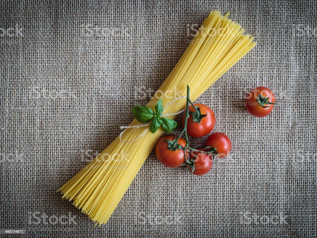 Spaghetti, cherry tomatoes and basil on jute fabric stock photo