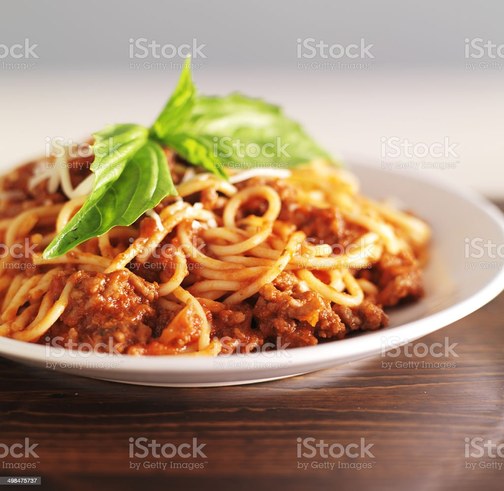 spaghetti dinner with meat sauce and basil stock photo