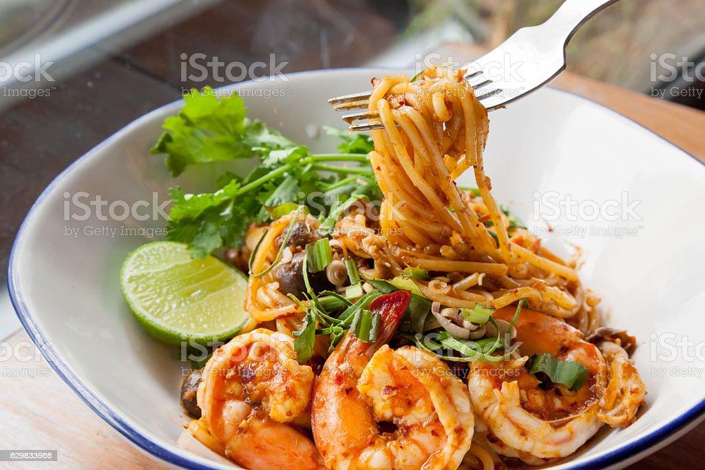 Spaghetti fried with sour prawn soup stock photo