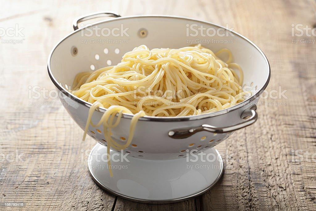 spaghetti in colander stock photo