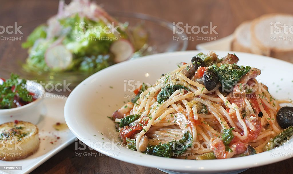 Spaghetti in tomato sauce in white bowl with other dishes royalty-free stock photo