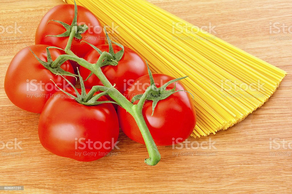 spaghetti pasta and tomatoes at branch close-up on wooden board stock photo