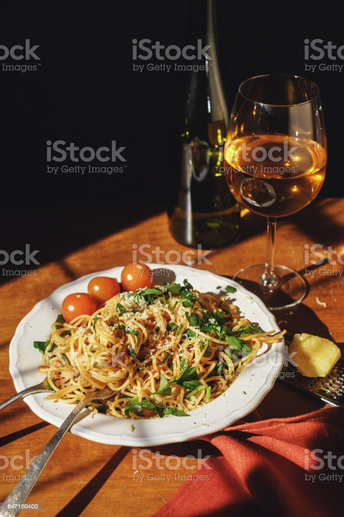 Spaghetti with cherry tomartoes served on a wooden table. stock photo