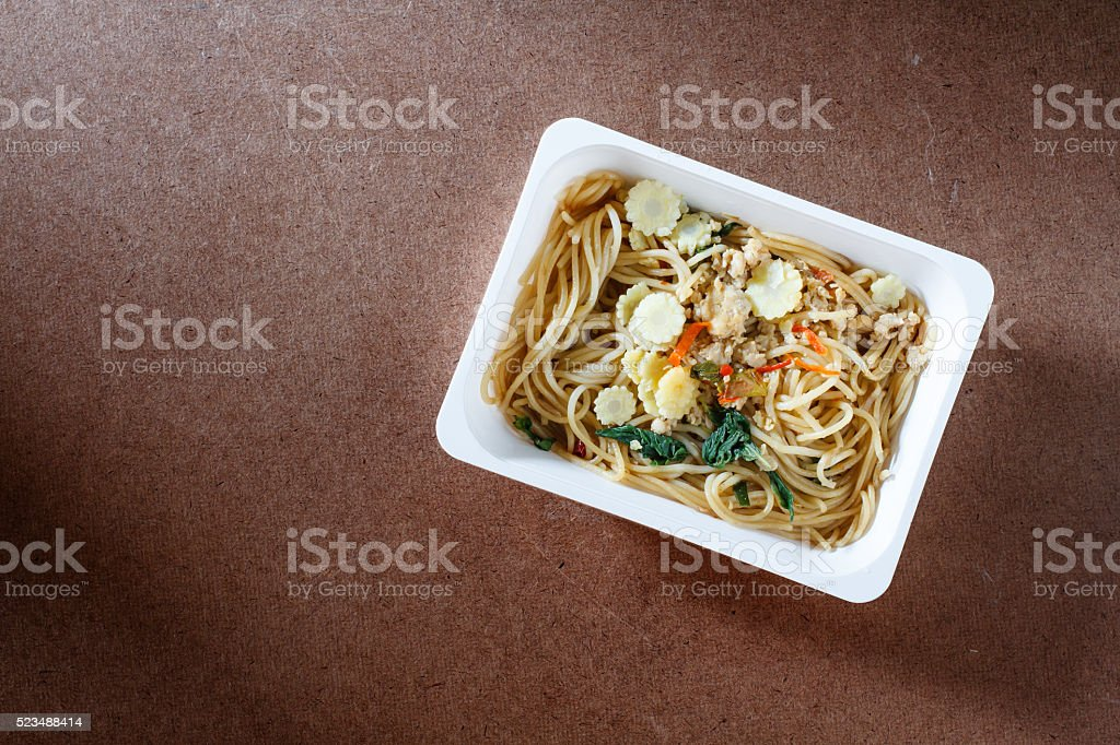 Spaghetti with chili pork basil leaf in food container.Top view. stock photo