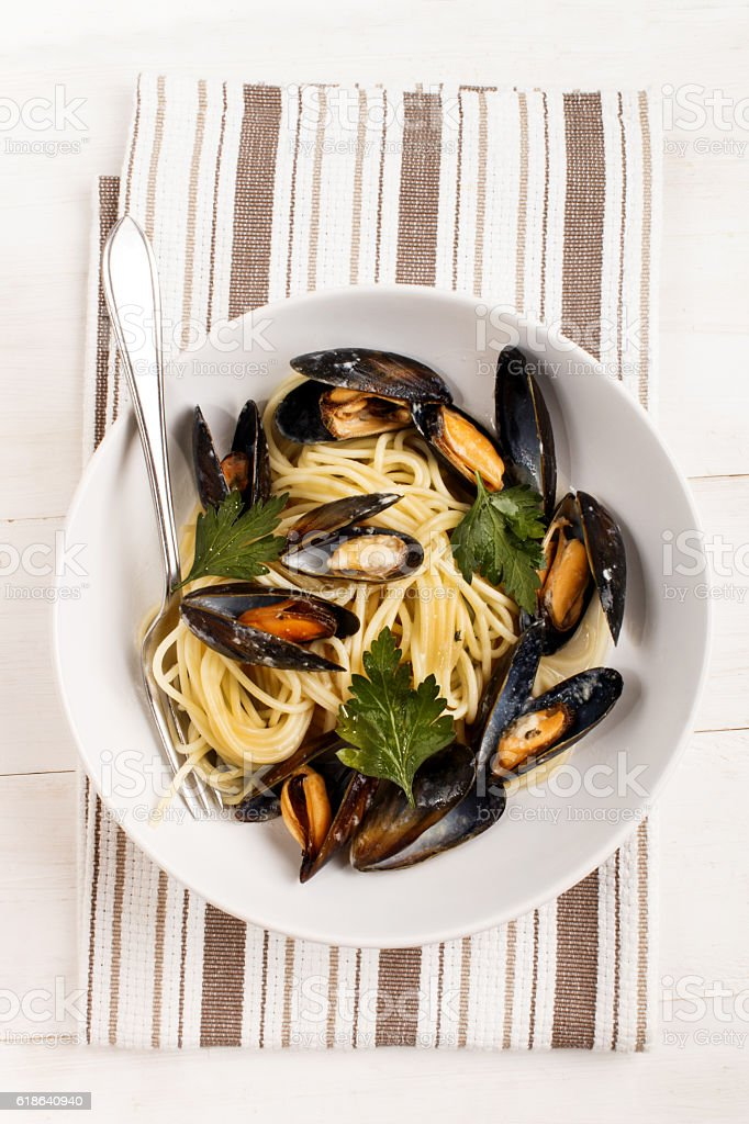 spaghetti with cooked  mussels  in a white wine sauce stock photo