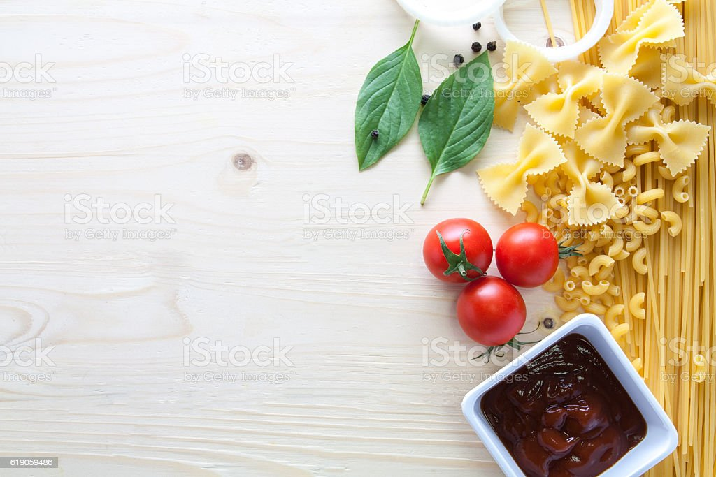 spaghetti with ingredients for cooking on wood background stock photo