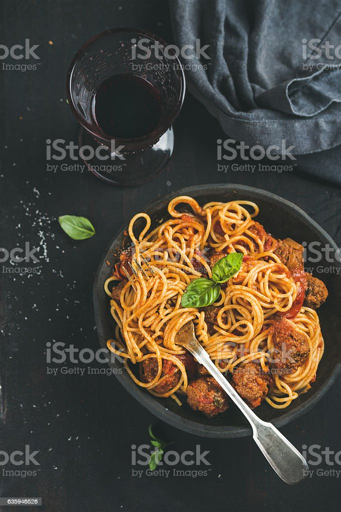Spaghetti with meatballas, fresh green basil leaves and red wine stock photo
