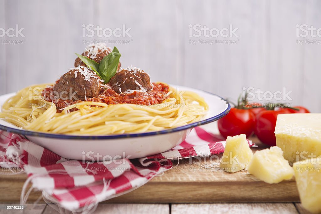 Spaghetti with meatballs and parmesan cheese on a rustic table stock photo