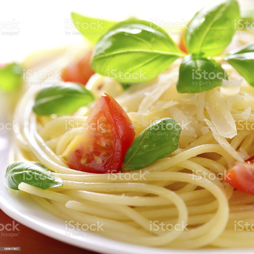 Spaghetti with parmesan cheese, fresh tomatoes and basil royalty-free stock photo