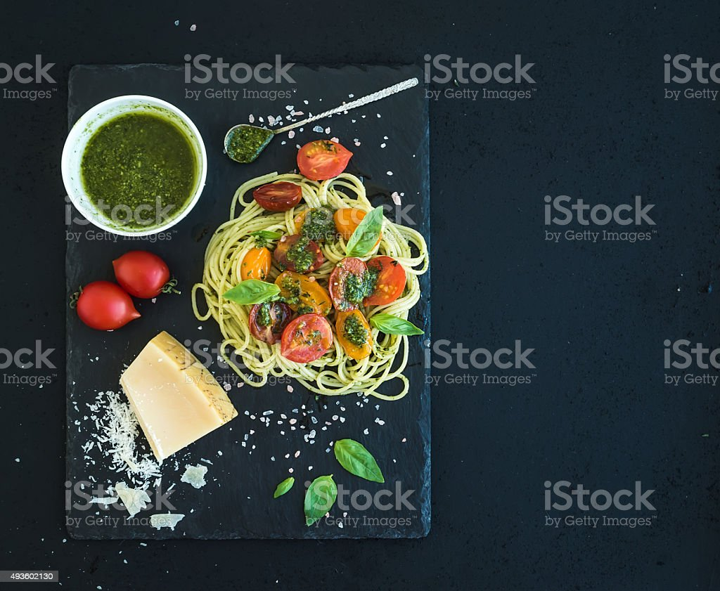 Spaghetti with pesto sauce, roasted cherry-tomatoes, fresh basil and stock photo