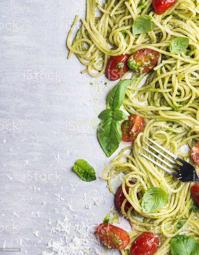 Spaghetti with pesto sauce, roasted cherry-tomatoes, fresh basil and stock photo