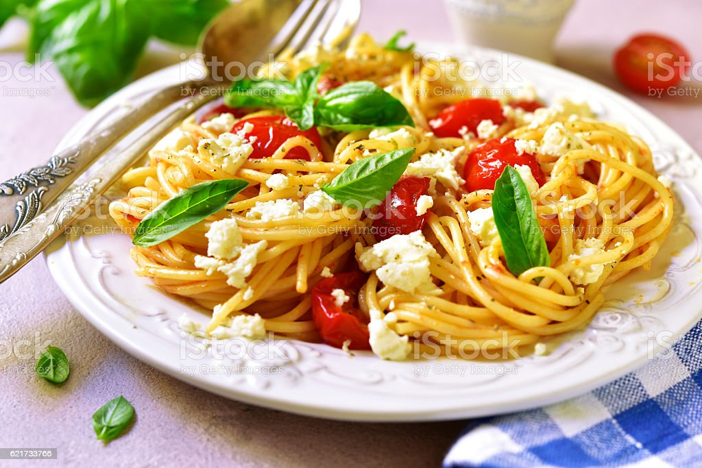 Spaghetti with tomatoes and ricotta in a red sauce. stock photo