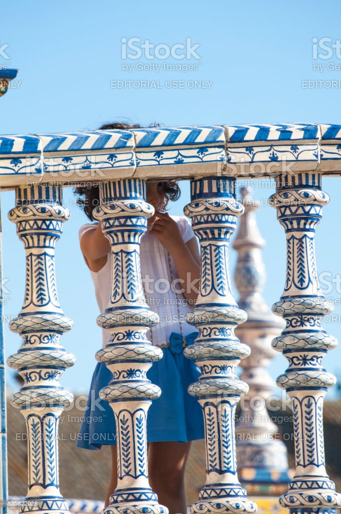 Spain: a baby girl playing hide and seek behind the columns of a bridge in Plaza de Espana, the most famous square of Seville stock photo