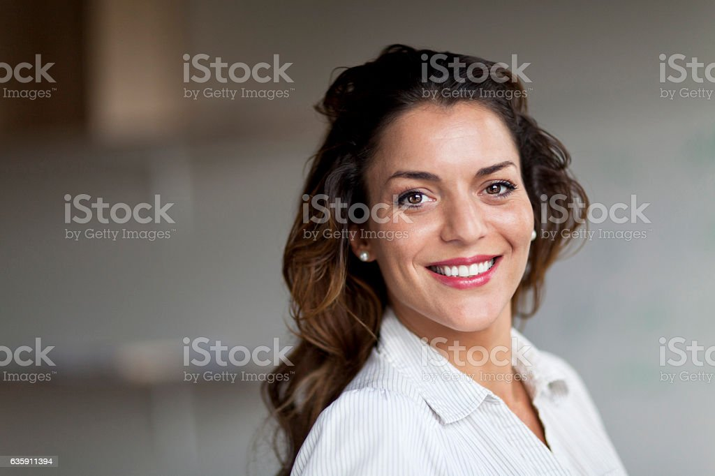 Spanish Businesswoman Smiling At the Camera. At the office. stock photo