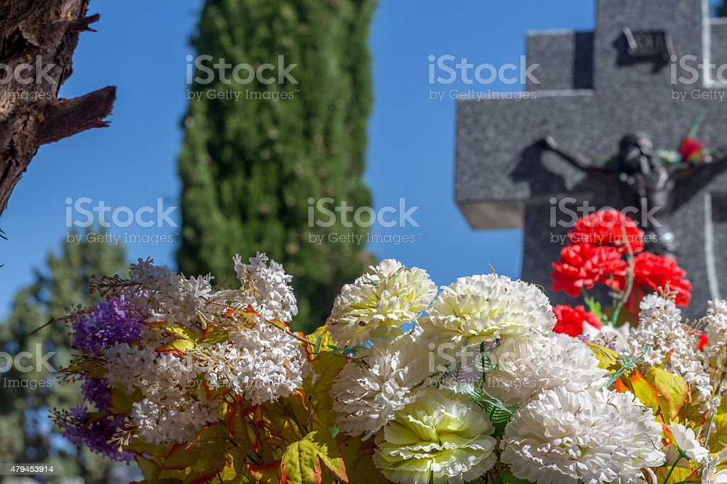 Spanish cemetery, cross with Jesus Christ and flowers stock photo
