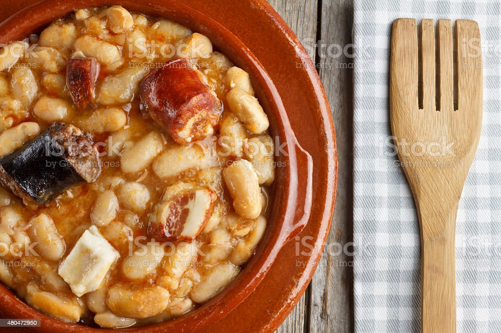 Spanish fabada in an earthenware dish and a wooden fork stock photo