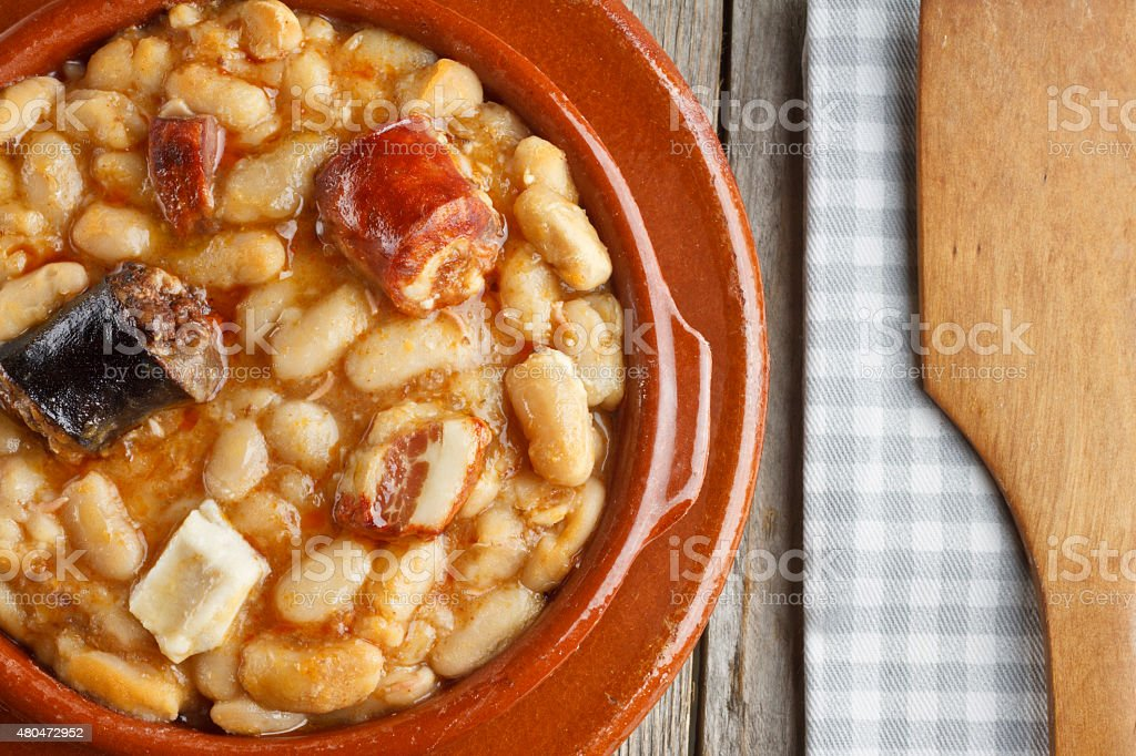 Spanish fabada in an earthenware dish and a wooden spoon stock photo
