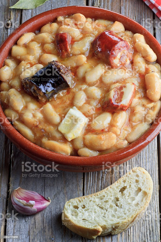 Spanish fabada in an earthenware dish with bread and garlick stock photo