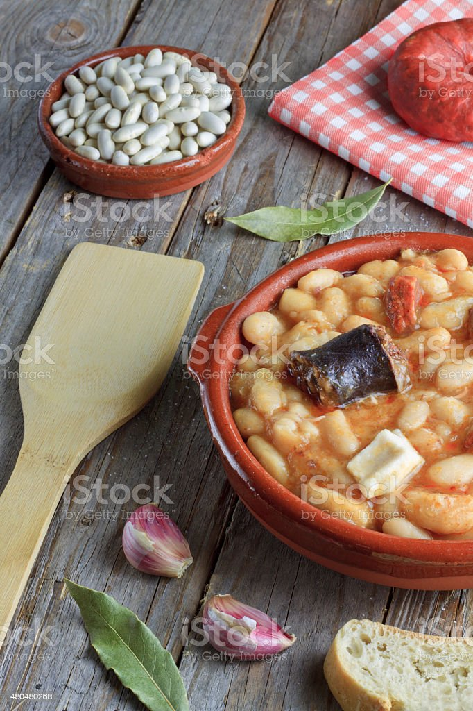Spanish fabada in an earthenware dish with ingredients stock photo