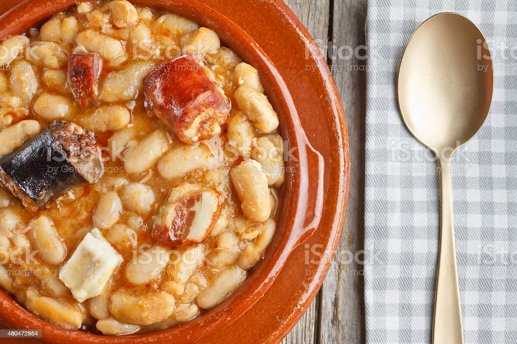 Spanish fabada in earthenware dishes with a golden spoon stock photo
