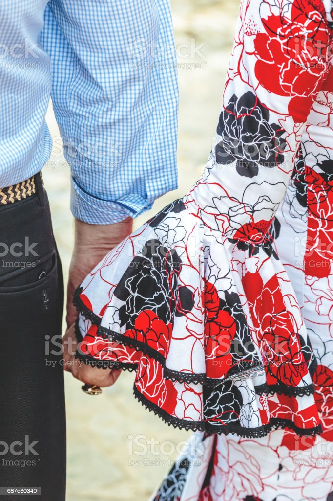 Spanish flamenco dress. Young couple holding hands. stock photo