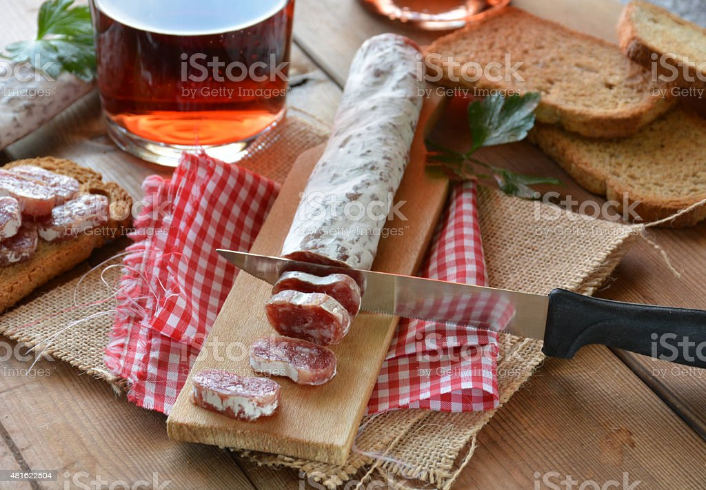 Spanish fuet salami on a cutting board stock photo