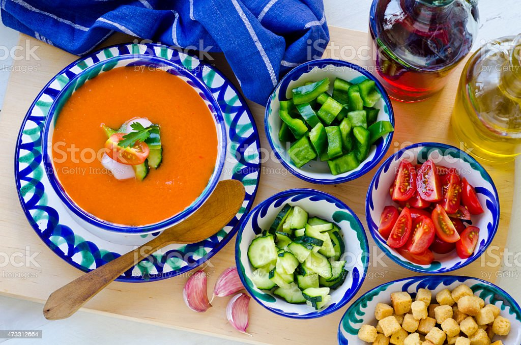Spanish gazpacho and its ingredients in blue bowls stock photo