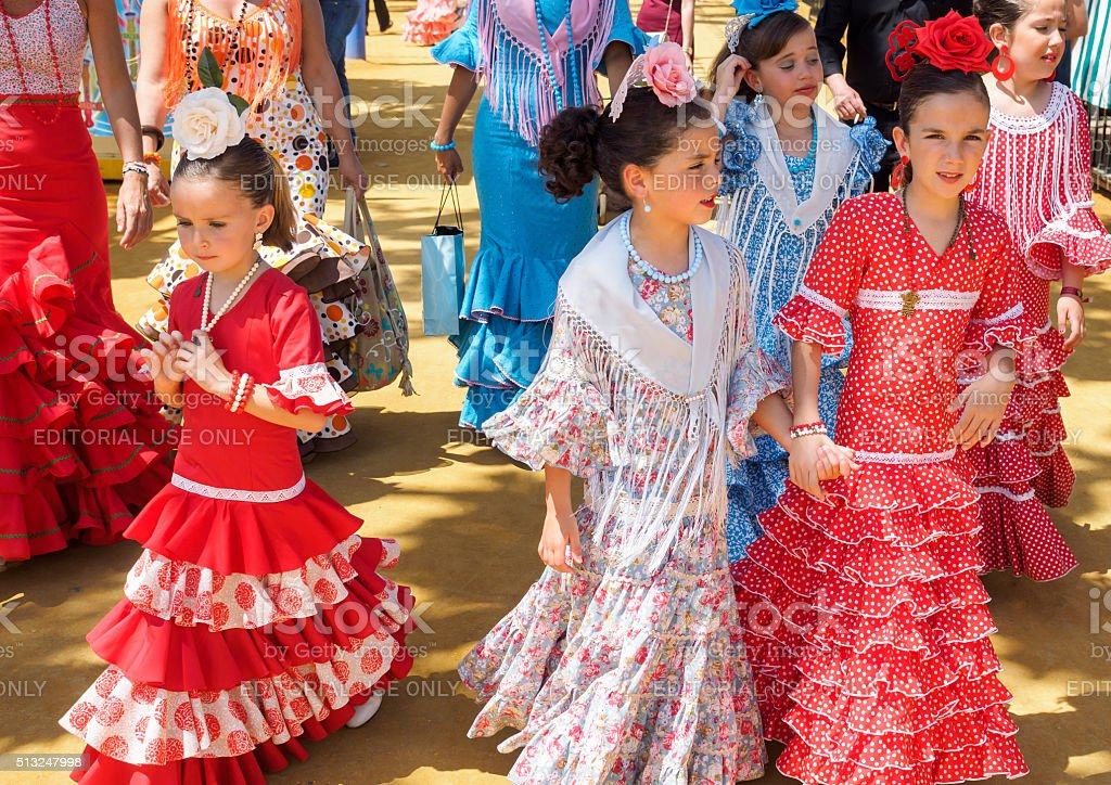 Spanish girls in traditional dress walking at the Seville Fair stock photo