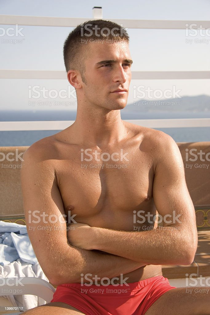 Spanish guy sitting at pool with arms crossed royalty-free stock photo