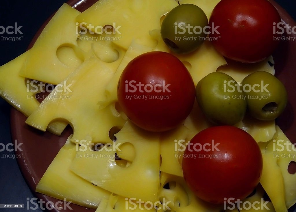 Spanish olives, swiss cheese and italian tomatoes on clay plate stock photo
