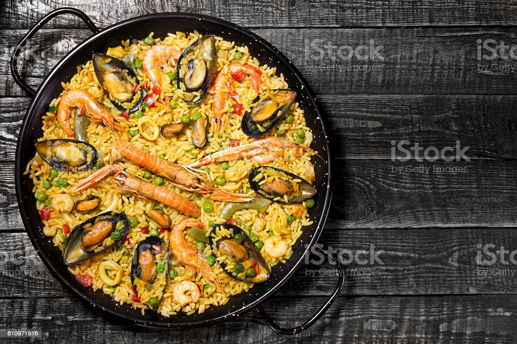 Spanish paella on a dark wooden table with copy space on the right