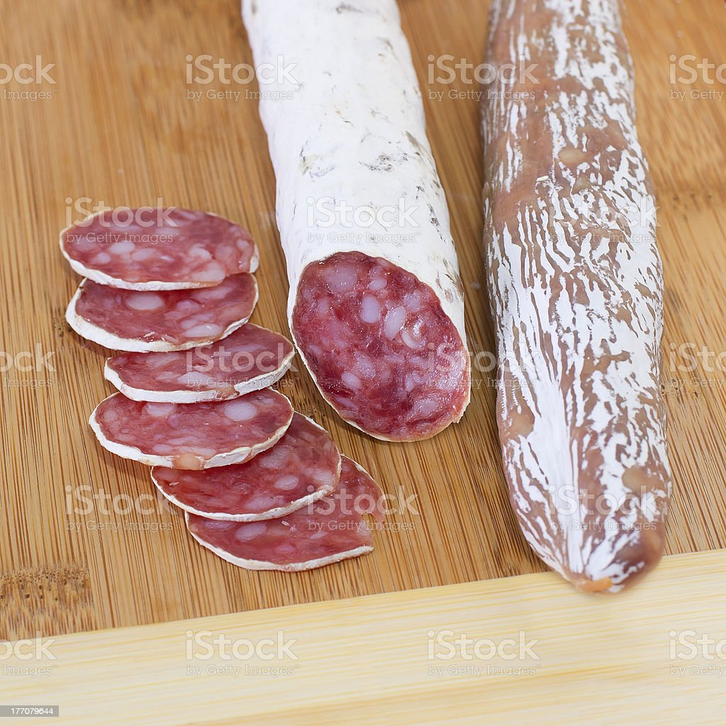 Spanish sausages fuet on wooden background. royalty-free stock photo