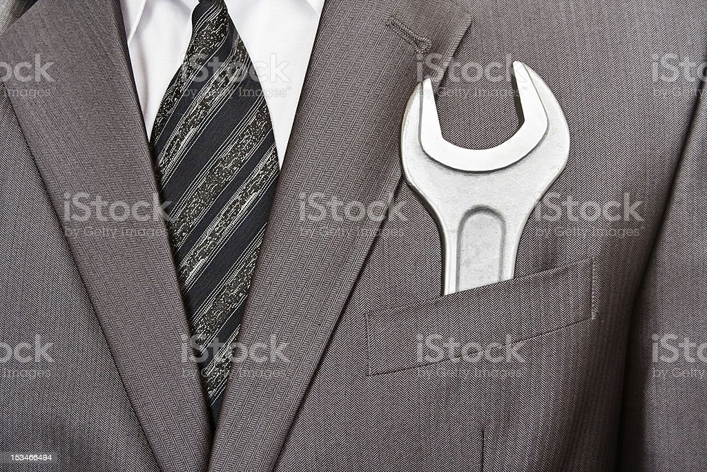 Spanner in businessman suit pocket stock photo