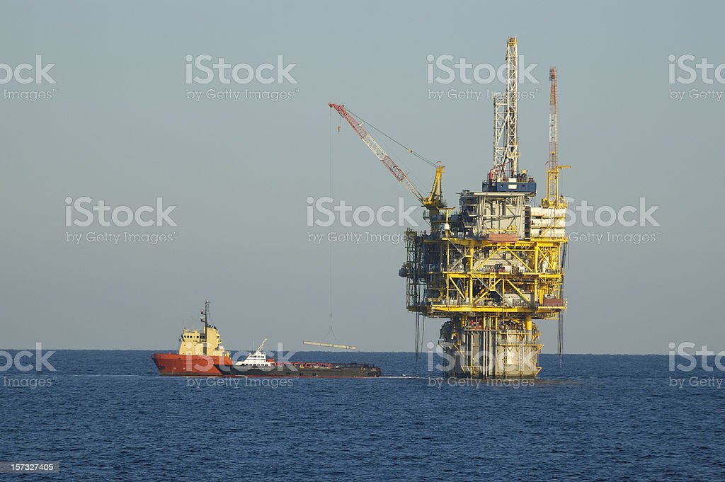 spar type production platform  and supply vessels. Oil rig. stock photo