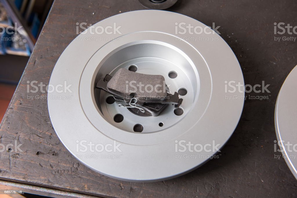 Spare part, new brake disc and brake lining on the workbench stock photo