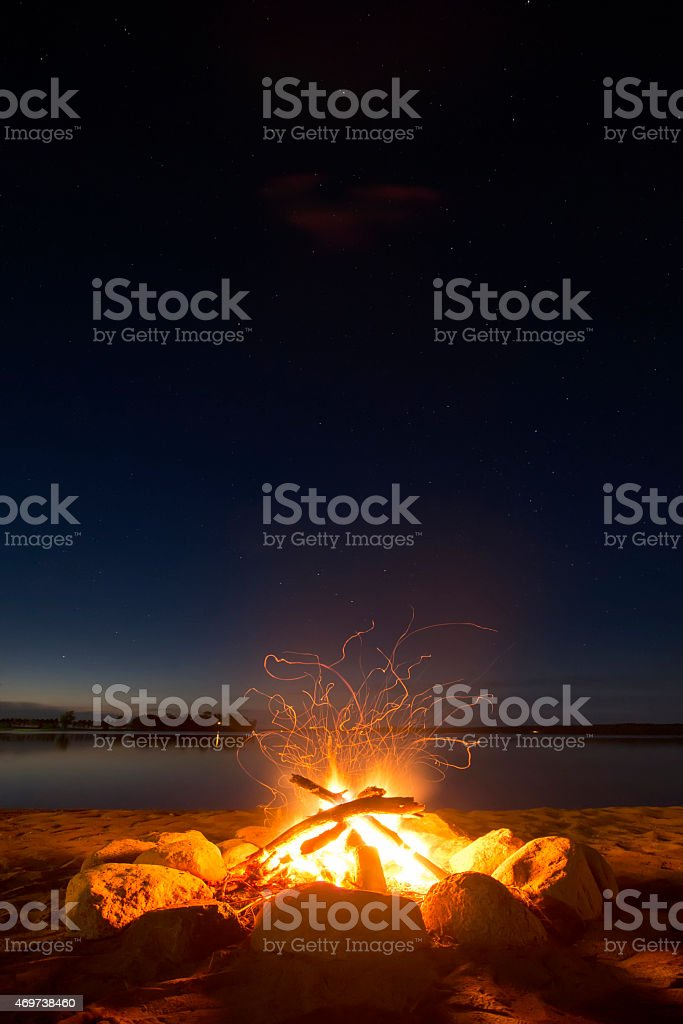 Sparking camp fire beside lake under a starry sky. stock photo