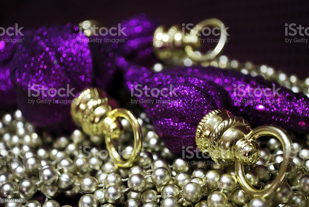Sparkle Purple Christmas Ornaments on Bed of Gold Beads stock photo