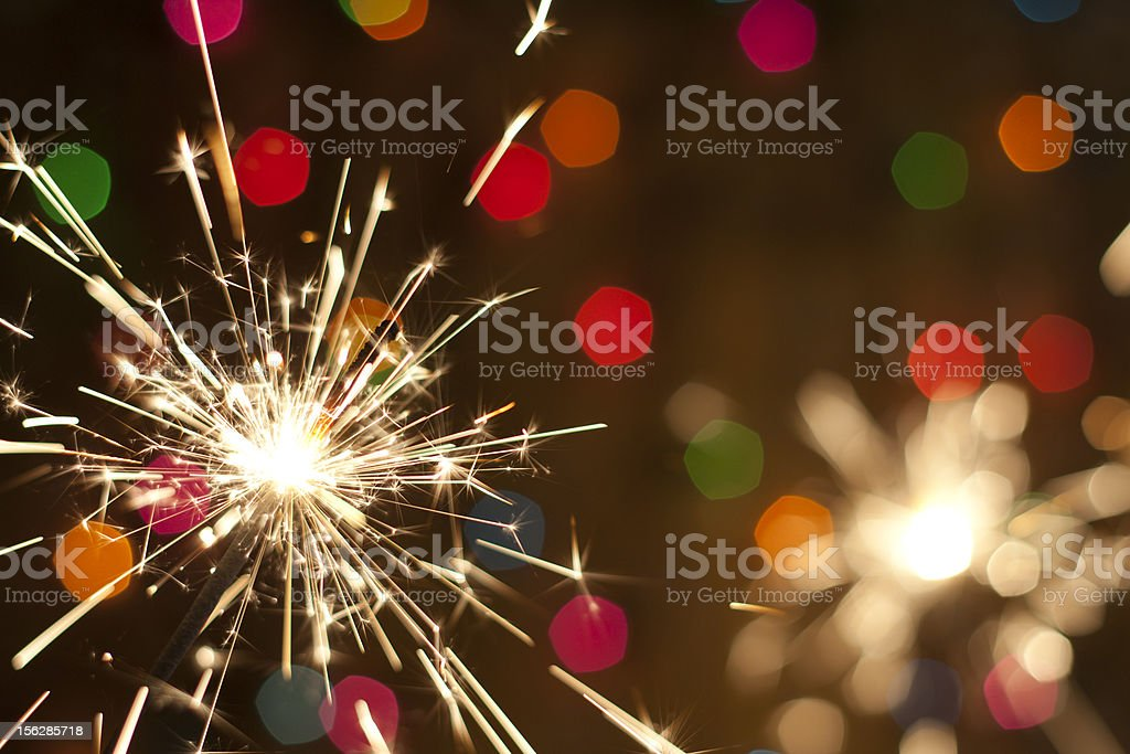 Sparkler and colorful bokeh stock photo