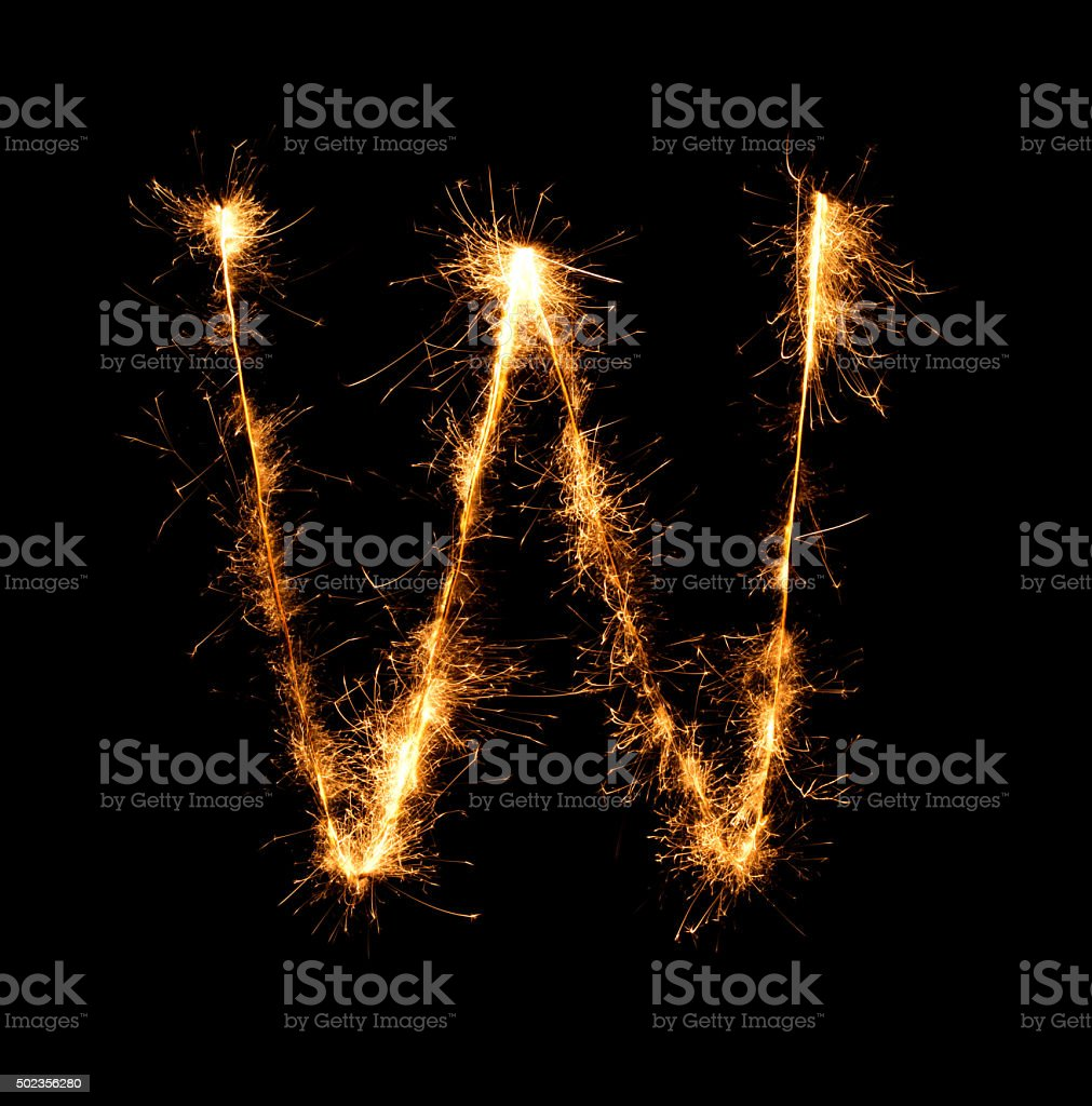 Sparkler firework light alphabet W at night stock photo